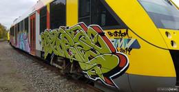 Illegaler Graffiti: Zug im Bahnhof mit Farbe besprüht